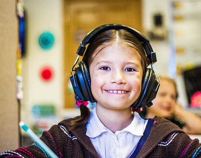 girl with headphones looking at the viewer and smiling